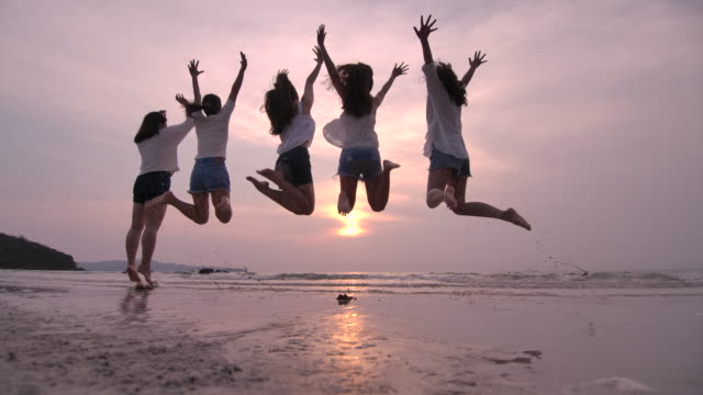 Silhouette of group of Woman smiling friends jumping together on the beach in summer