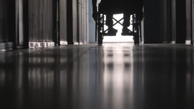 siluett av handikappade patienten rider rullstol längs korridoren - hospital studio bildbanksvideor och videomaterial från bakom kulisserna