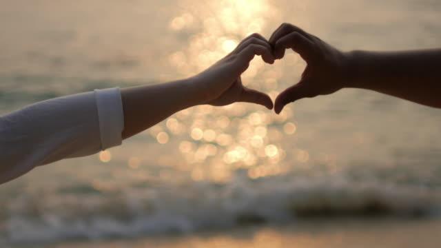 シルエットを手愛好家ビーチの日没に時間を作るハート形愛とウェディングコンセプト、4 K (UHD ビデオ