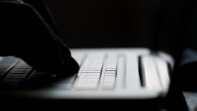 silhouette of hands on keyboard of modern laptop. fingers typing text. close up - anonymous hackers stock videos and b-roll footage