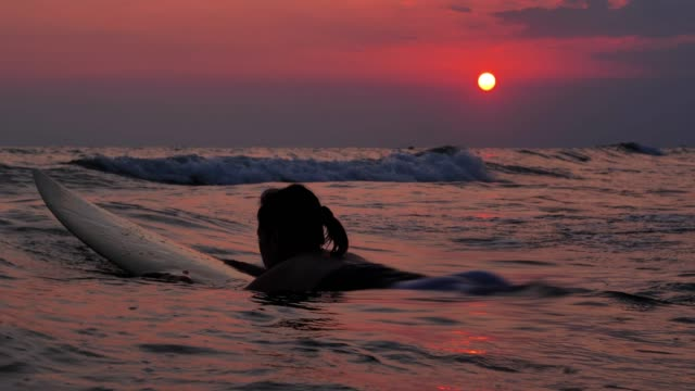 Silhouette of happy beautiful sexy surfer girl on the surfboard and waiting for the waves.on the beach at sunset.Sports Cinemagraphs,Vacations - iStock