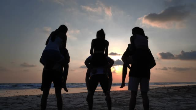Silhouette of happy boyfriends piggybacking their girlfriends and laughing together during summer holidays vacation on tropical beach.Vacations - iStock
