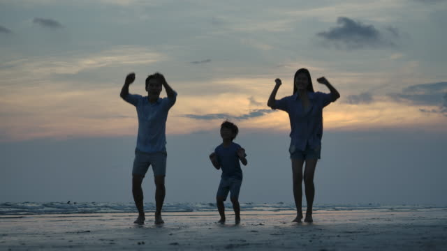 Silhouette of happy family jumping on the beach with sunset background, slow motion. Family, Freedom and Travel concept.