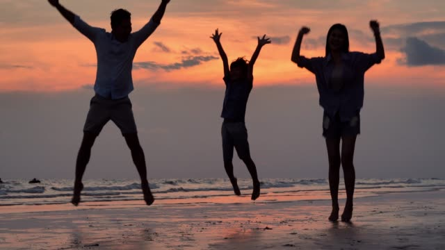 Silhouette of happy family jumping together on the beach.Happy family enjoy summer vacation on the beach.Vacations - iStock