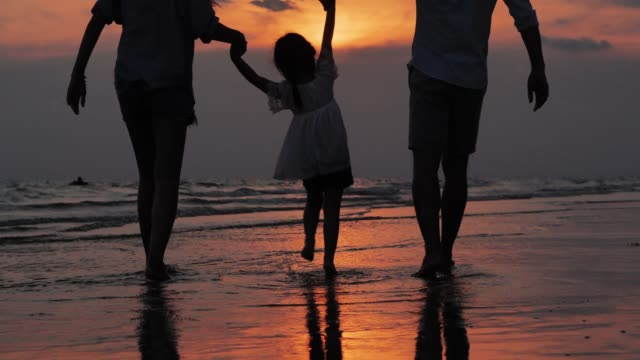 Silhouette of happy family walking together on the beach.Happy family enjoy summer vacation on the beach.Vacations - iStock Vacations :Silhouette of happy family walking together on the beach.Happy family enjoy summer vacation on the beach pacific islands stock videos & royalty-free footage