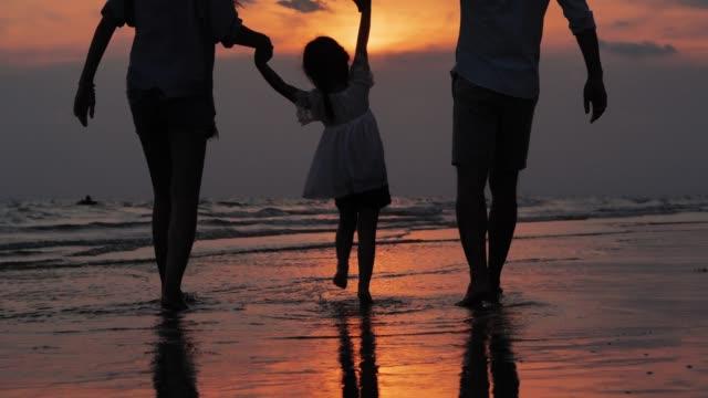vídeos de stock e filmes b-roll de silhouette of happy family walking together on the beach.happy family enjoy summer vacation on the beach.vacations - istock - oceano pacífico