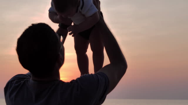 Silhouette of happy father and baby boy cheerful on the beach at sunset.,Family Relationship,Childhood and parenthood concept.South East and East Asia: Asian Babies