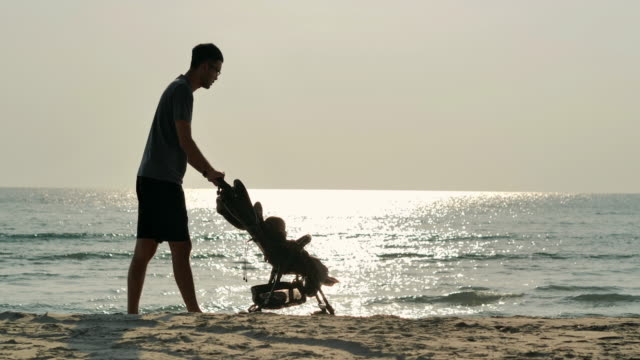 Silhouette of happy father and baby boy walking on the beach at sunset.Family,Lifestyle,People,South East and East Asia: Asian Babies