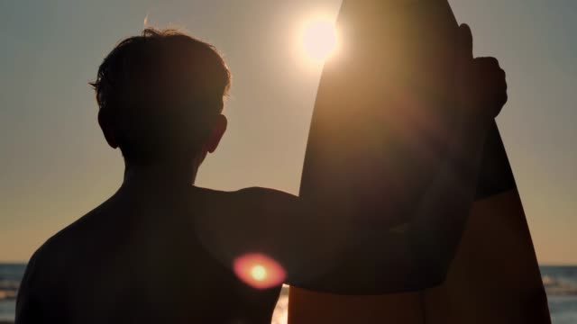 Silhouette of happy senior male surfer standing with surfboard on the beach.Real Bodies