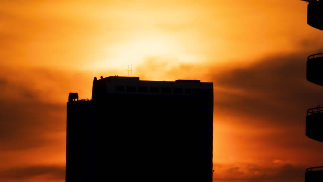 Silhouette of high building with some people on it and the sun in background