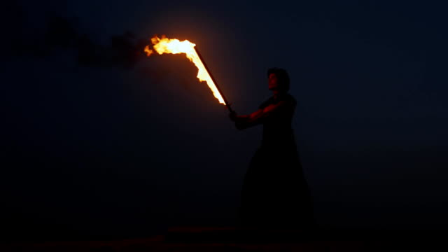 Silhouette of hispanic man with fire sword at night, martial arts, waving a sword video