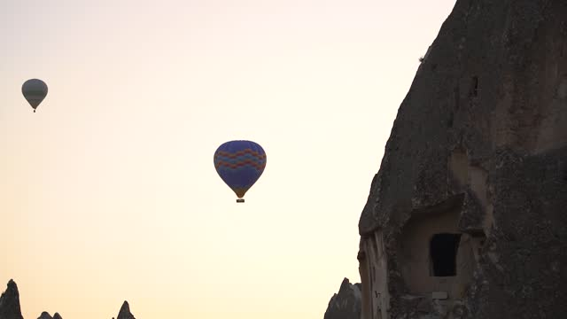 Silhouette of hot air balloon near mountain with cave house