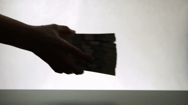 Silhouette of human hands give pile paper money to another person video
