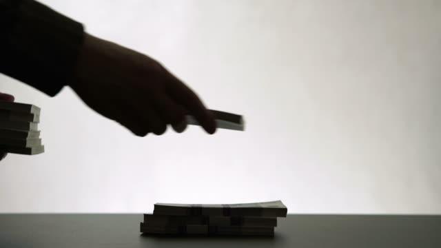 silhuetten av mänskliga händer lägger ut stack av pappers-pengar - kriminell bildbanksvideor och videomaterial från bakom kulisserna