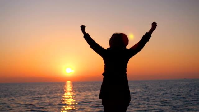 Silhouette of joyful woman at sunset video