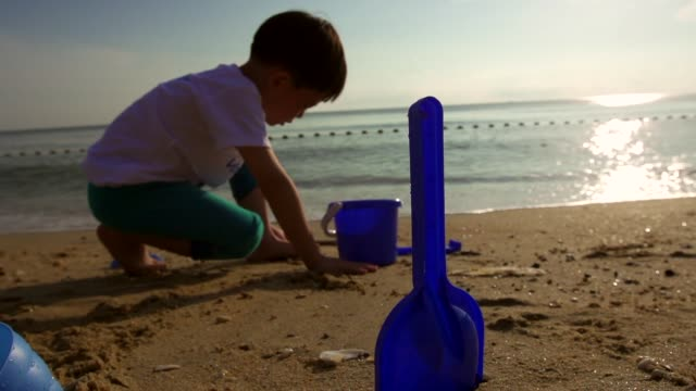 Silhouette of kid is playing sand at the beach in the morning.