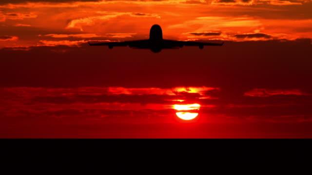 Silhouette of large passenger airplane taking off against orange sunset