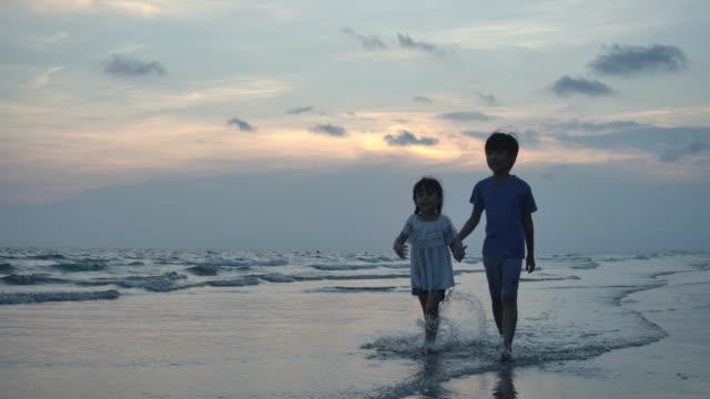 vídeos y material grabado en eventos de stock de silueta de la niña y su hermano caminando en la playa en la hora del atardecer. cámara lenta. concepto de familia, libertad y viajes. - hermana