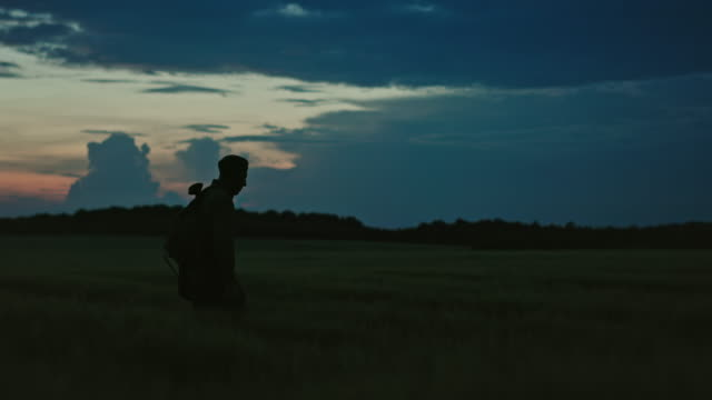 Silhouette of lonely soldier walking in field on red sunset background. A sad conceptual scene about the history of the soldiers of World War II and the Cold War