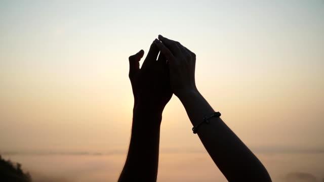silhouette di mani maschili e femminili che si tengono a vicenda sullo sfondo del tramonto. giovane coppia che unisce le braccia all'aperto. concetto di amore e felicità. coppia di amanti godendo di un bellissimo momento romantico. - braccio umano video stock e b–roll