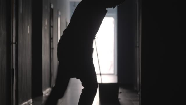 silhuetten av manliga vaktmästaren tvätta golvet i hallen - hospital studio bildbanksvideor och videomaterial från bakom kulisserna