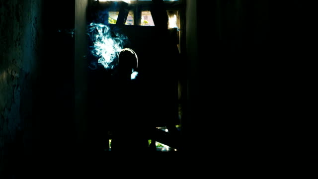 Silhouette of male smokers in an abandoned house. Concept: crime, danger video