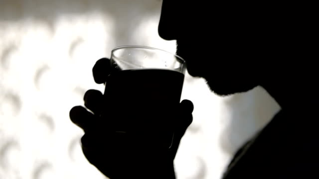 silhouette of man, addicted alcoholic, drinking short drink at home - anonymous hackers stock videos and b-roll footage
