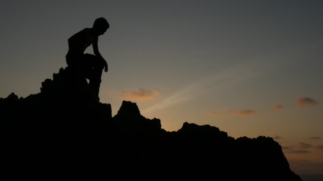A silhouette of man climbing on stone, mountain at sunset video