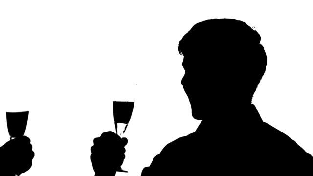 silhouette der mann paar clinking brille wein, zeitlupe - champagner toasts stock-videos und b-roll-filmmaterial
