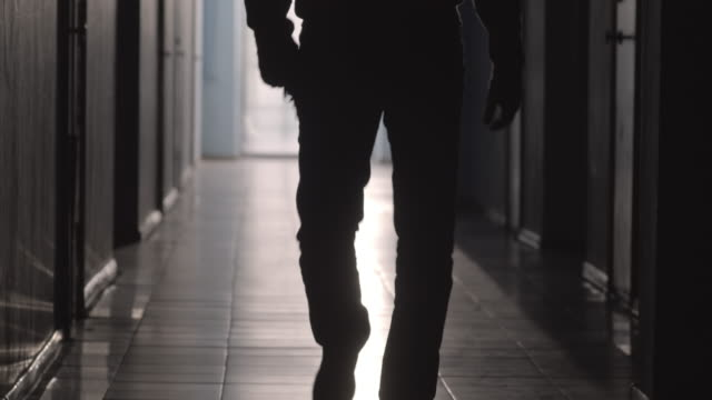 Silhouette of Man Going with Handgun Tilt up shot of silhouette of unrecognizable man walking with handgun along dark hallway crime stock videos & royalty-free footage