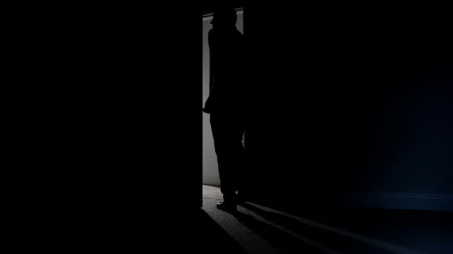 Silhouette of man leaving dark room. video