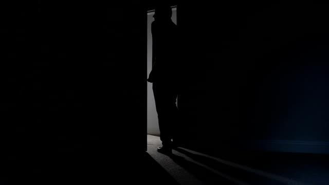 vídeos y material grabado en eventos de stock de silueta de hombre salir sala oscura. - despedida