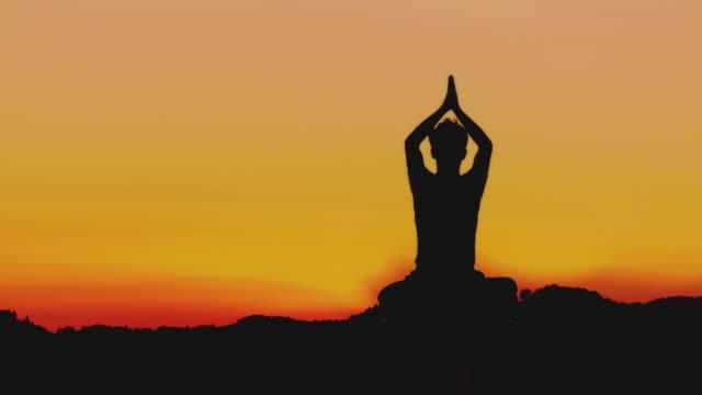 ws silhouette of man meditating in lotus pose at sunset, horjul, slovenia - lotusställning bildbanksvideor och videomaterial från bakom kulisserna