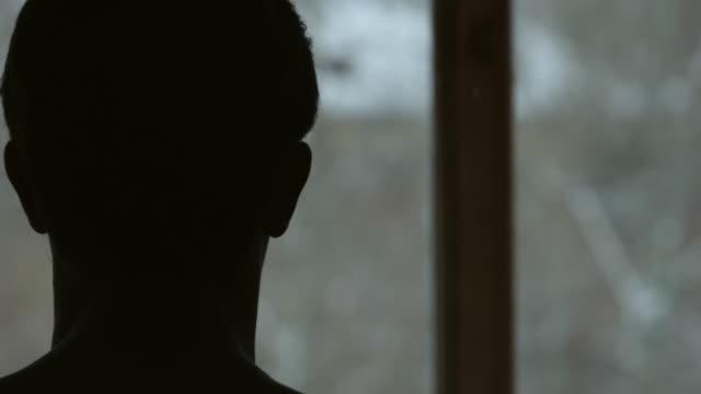 sagoma dell'uomo vicino alla finestra - controluce video stock e b–roll