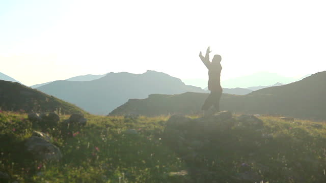 Silhouette of man practicing martial arts in mountains, exercise video