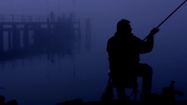 silhuetten av mannen sitter vid bron och fiske - meta bildbanksvideor och videomaterial från bakom kulisserna