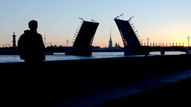 vita nätter: silhuetten av mannen står och öppnade palace bridge - st. petersburg, ryssland - peter and paul cathedral bildbanksvideor och videomaterial från bakom kulisserna