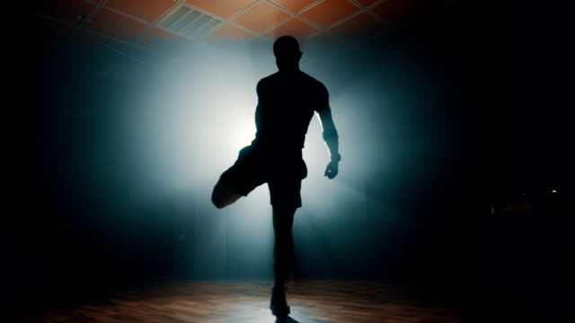 Silhouette of man stretching before workout There is one young man, age 35. He is a trainer of freestyle workout. He is in his hall, and he doing his workout. sportsperson stock videos & royalty-free footage