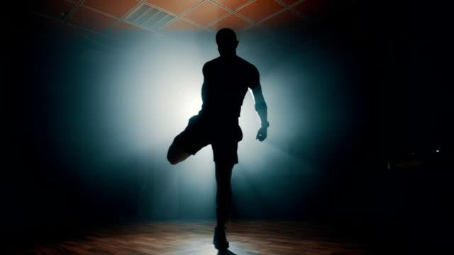 silhouette of man stretching before workout - rozgrzewka filmów i materiałów b-roll