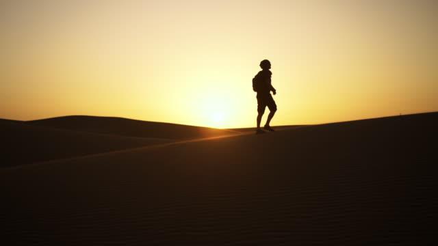 Silhouette Of Man Walking Along Sand Dunes