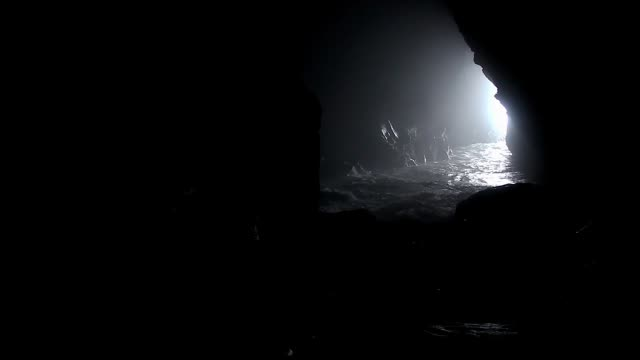 Silhouette of man walking towards water on sea cave Waves entering through dark cavern. Creepy, risky, frightening, natural landscape concepts cave stock videos & royalty-free footage