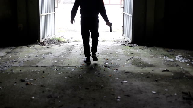 vídeos de stock e filmes b-roll de silhouette of man walks out of large entrance of spooky, abandoned building holding handgun replica in his hand - capuz