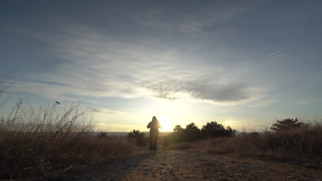 Silhouette of man with backpack on trail against the rising sun.