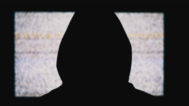 vídeos de stock e filmes b-roll de silhouette of man's head in hood is watching white static noise and tv interference - capuz
