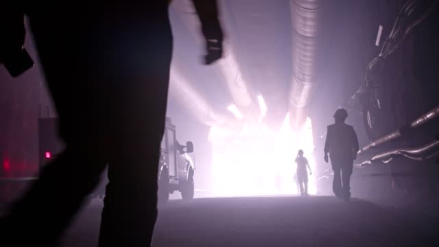 silhouette of many construction workers walking out from a large tunnel - sottosuolo video stock e b–roll