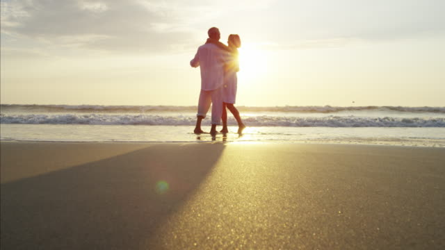 Silhouette of mature Caucasian couple dancing on beach
