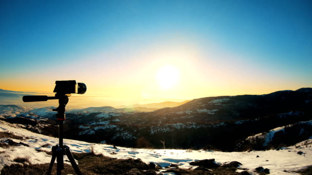 Silhouette of mirrorless camera on tripod on sunset background. Shooting rural landscape at sunset