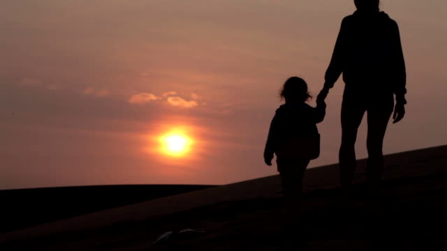 Silhouette of mother holding her baby child hand and going away from camera video