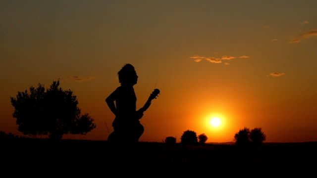 Silhouette of musician running at  twilight time video