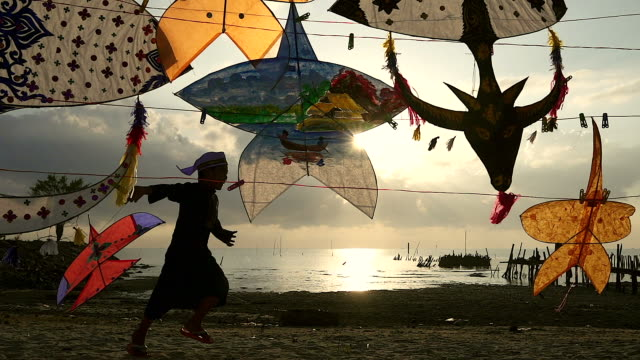 silhouette of muslim child flying a kite with the traditional kite as foreground. - malese video stock e b–roll